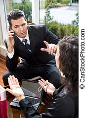 Businessman listening to mobile phone in meeting