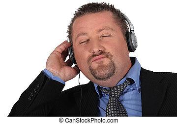 Businessman listening to music on white background