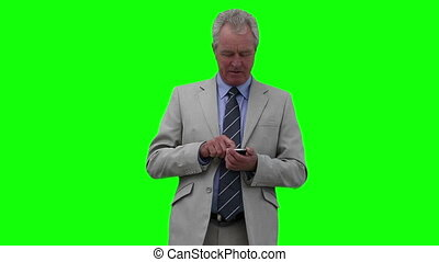 Businessman looking around while typing on his phone