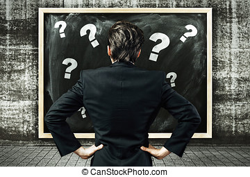 Businessman looking at a billboard with chalk drawn question marks