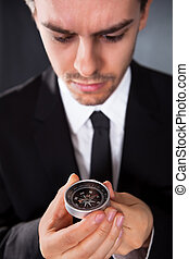 Businessman looking at a compass