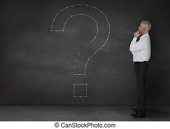 Businessman looking at a giant question mark drawn on the wall