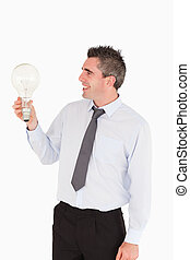 Businessman looking at a light bulb against a white background
