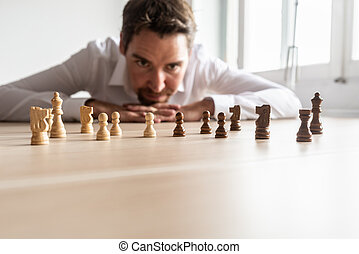 Businessman looking at black and white chess pieces on office desk