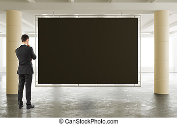 Businessman looking at blank blackboard in sunny spacious hangar area with concrete floor, mock up