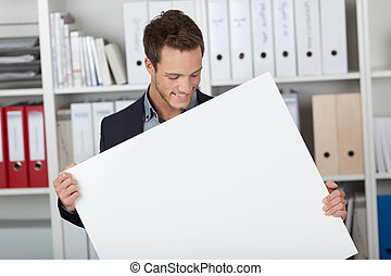 Businessman Looking At Blank Sign At Office