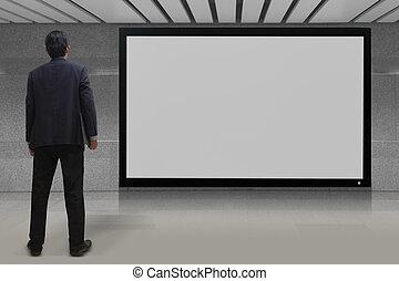 Businessman looking at blank TV screen