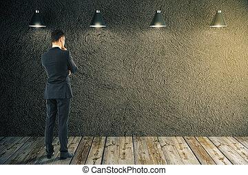 Businessman looking at blank wall