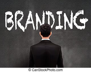 businessman looking at branding word on wall