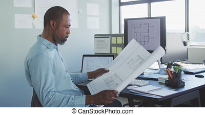Businessman looking at building project in modern office