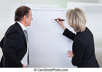 Businessman Looking At Businesswoman Writing On Flipchart