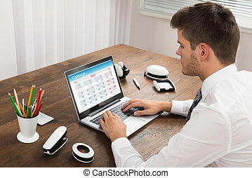 Businessman Looking At Calendar On Laptop In Office