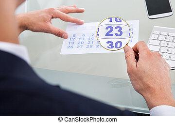 Businessman Looking At Calendar Through Magnifying Glass