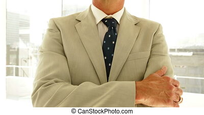 Businessman looking at camera with arms crossed in his...