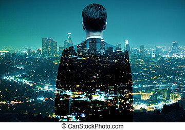 Businessman looking at illuminated night city. Double exposure