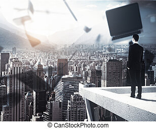 Businessman looking at city with laptop