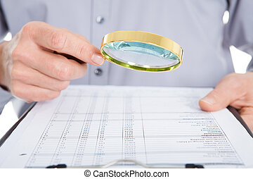 Looking At Document Through Magnifying Glass