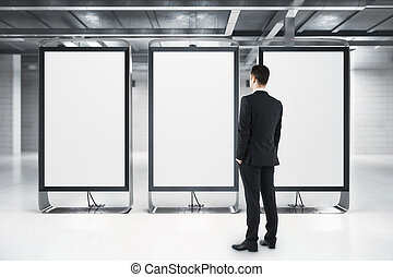 Businessman looking at empty posters