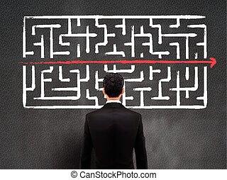 businessman looking at hand drawn maze