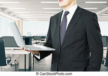 Businessman looking at he laptop in modern open space office