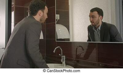 Businessman looking at himself in mirror to encourage and...