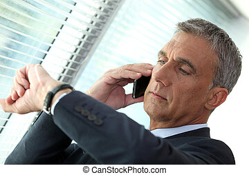 Businessman looking at his watch whilst on the phone