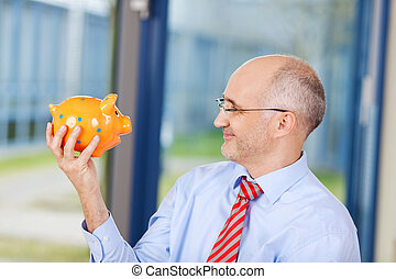 Businessman Looking At Piggybank In Office