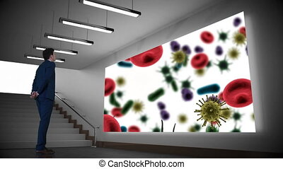 Businessman looking at projector screen with bacteria
