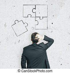 businessman looking at puzzle parts