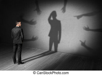 Businessman looking at shadow where many hands reach for him...