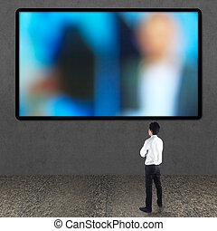 Businessman looking at TV screen