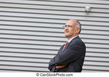 Businessman Looking Away Against Shutter