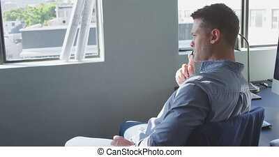 Businessman looking away in modern office - Side view of a ...