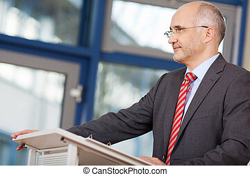 Businessman Looking Away While Standing At Podium -...