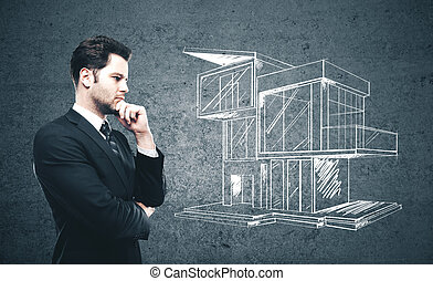 Businessman looking on drawing cottage