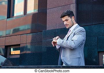 Businessman looking on wrist watch outdoors near office...