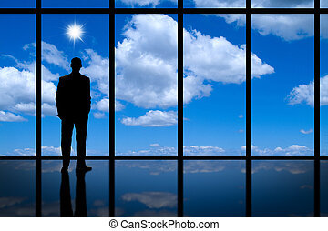 Business man looking out of highrise building window with blue sky, clouds and bright sunshine