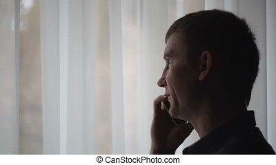 Businessman looking out the window and talking on the phone