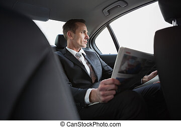Businessman looking out the window in his car