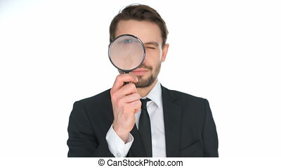 Businessman looking through a magnifying glass