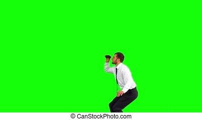 Businessman looking through binoculars while leaping on...