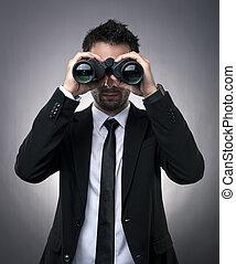 Businessman looking through binoculars - Young businessman...
