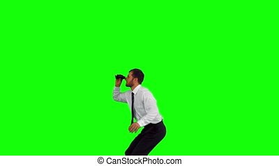 Businessman looking through binoculars while jumping up on...