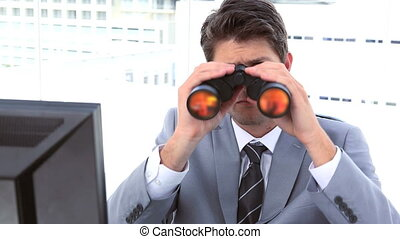 Businessman looking through binoculars while sitting at his...