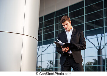 Businessman looking through documents while standing outdoors at the office