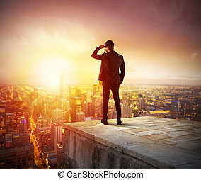 Businessman looks at the city during sunset. Future and new business opportunity concept