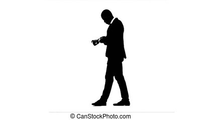 Businessman looks at a wrist watch and waits for partners. White background. Silhouette