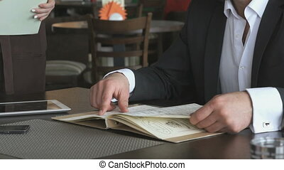 Businessman looks at food menu of the restaurant
