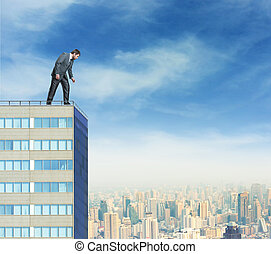 Businessman looks down from a high building