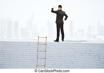 Businessman looks into the distance on the top of white brick wall with wooden ladder